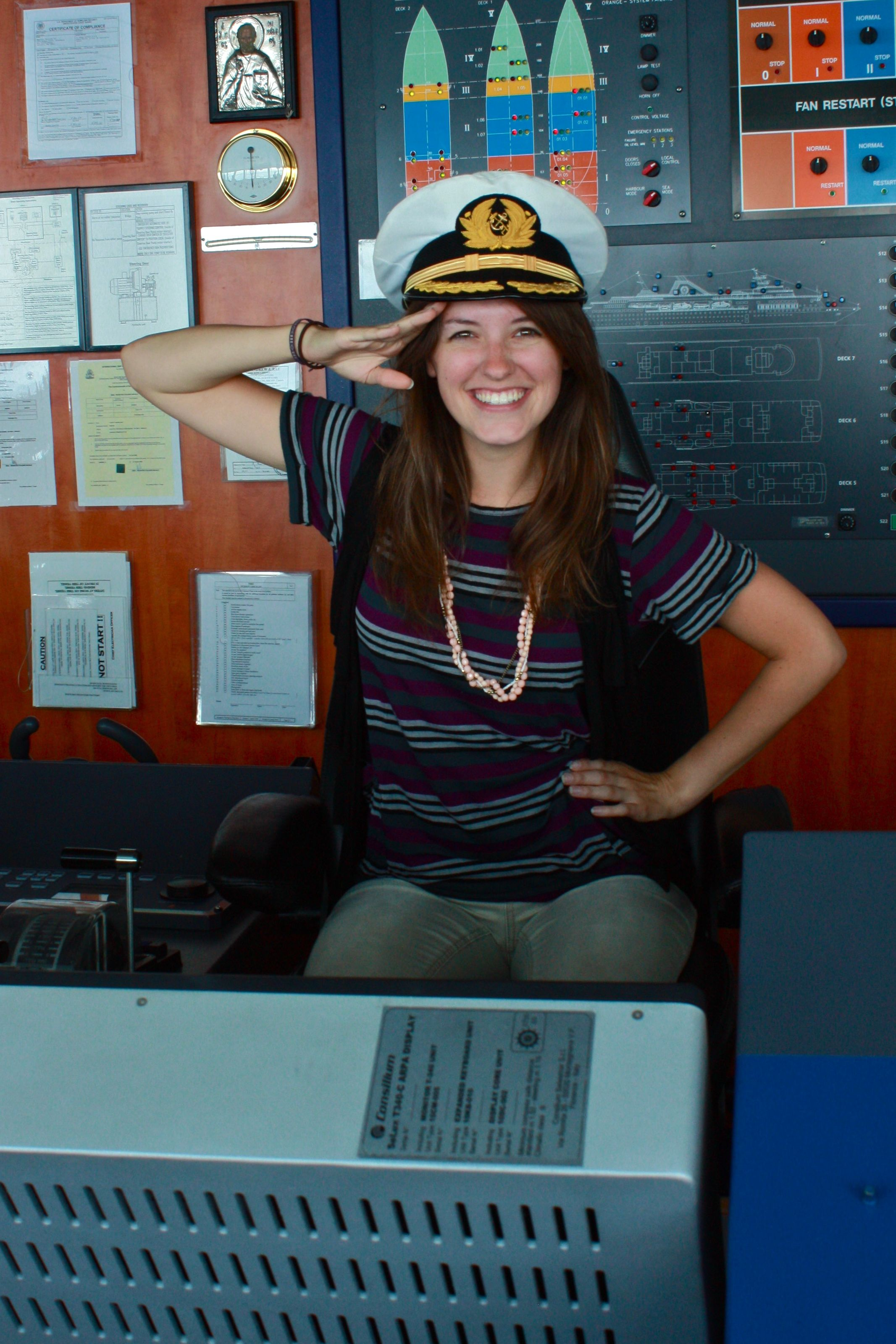 Young Women Saluting in Cruise Ship Bridge with Captain Hat