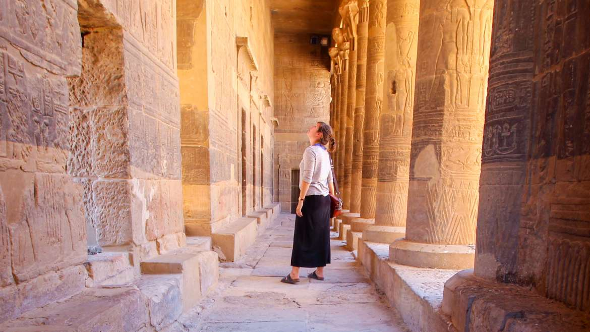 Woman looking at hieroglyphics in ancient Egypt temple